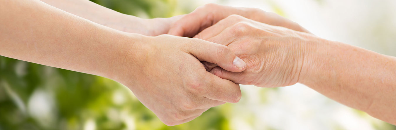 younger person holding hands with older person